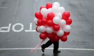 Image: A man carries a bunch of ballons as he walks down Union Street on Valentine's Day
